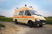 Foto: Krankenwagen von vorn vor einem Rapsfeld.